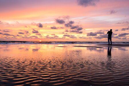 photographer at beach against sunset
