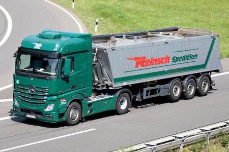 Reinsch Mercedes-Benz Actros truck with tipper trailer on motorway.