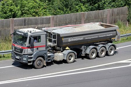 Schretzmair MAN TGS truck with tipper trailer on motorway.