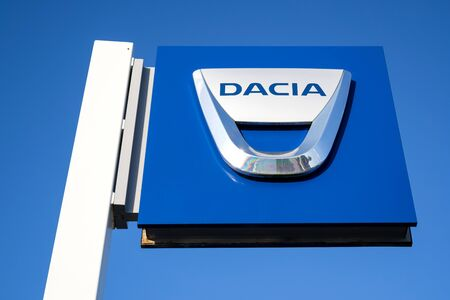 Dacia dealership sign against blue sky. 報道画像
