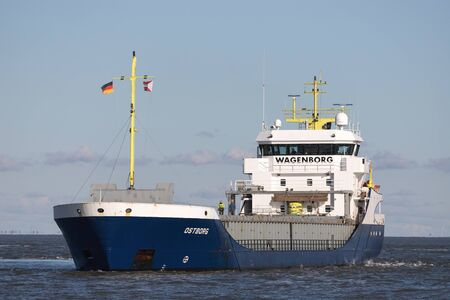 Wagenborg general cargo vessel OSTBORG on the river Elbe. Founded in 1898, Royal Wagenborg is an international maritime logistics conglomerate.