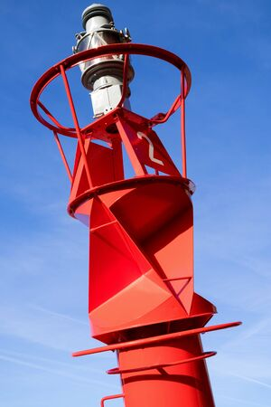 red lateral buoy against blue sky Imagens