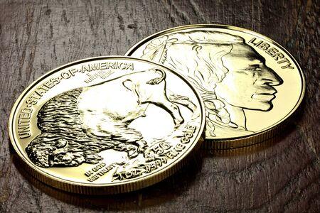 1 ounce American Buffalo gold bullion coins on wooden background