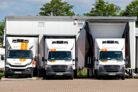trans-o-flex delivery vans docked at warehouse