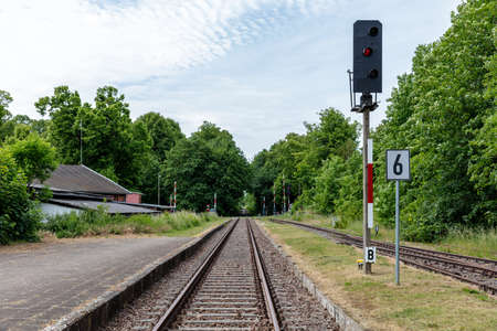 red railway signal at rail track