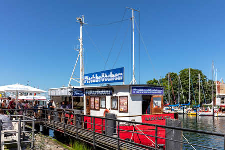 fish bar 'Futterkutter' at the canal called 'Alter Strom' (Old Channel) in the Warnemünde district of the city of Rostock in Mecklenburg, Germany Éditoriale