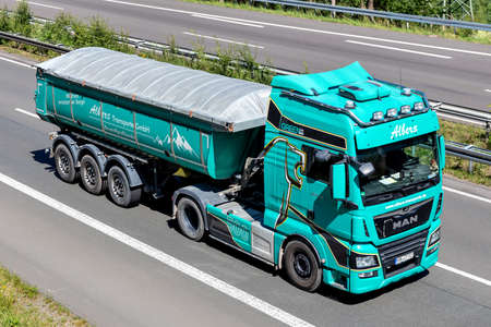 Albers MAN TGX truck with tipper trailer on motorway.