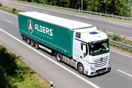 Alders Mercedes-Benz Actros truck with curtainside trailer on motorway. Editoriali