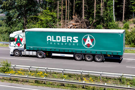Alders DAF XF truck with curtainside trailer on motorway. Editoriali