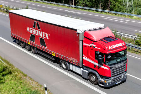 Agromex Scania R410 truck with curtainside trailer on motorway.