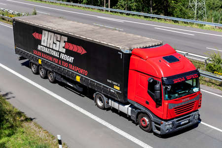 Siem Sped Iveco Stralis truck with BASE curtainside trailer on motorway.