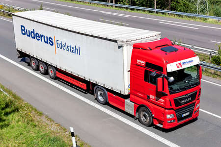 Strieder MAN TGX truck with Buderus curtainside trailer on motorway.