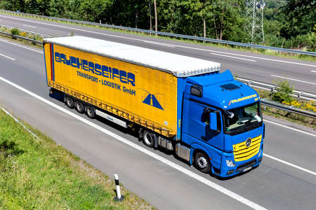 Brucherseifer Mercedes-Benz Actros truck with curtainside trailer on motorway.