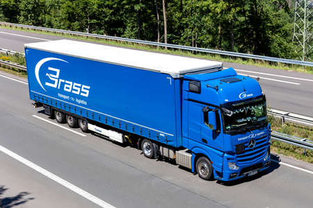Brass Mercedes-Benz Actros truck with curtainside trailer on motorway. Editoriali