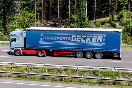 Scania truck with Transporte Decker curtainside trailer on motorway.