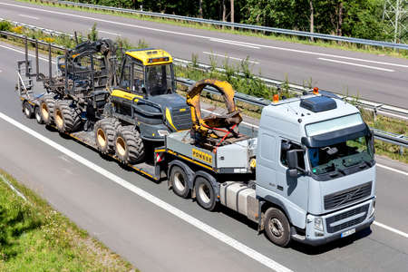 Ponsee Volvo FH flatbed truck with forestry machine on motorway.
