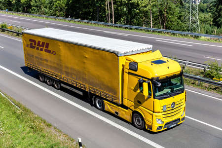 Mercedes-Benz Actros truck with DHL curtainside trailer on motorway.
