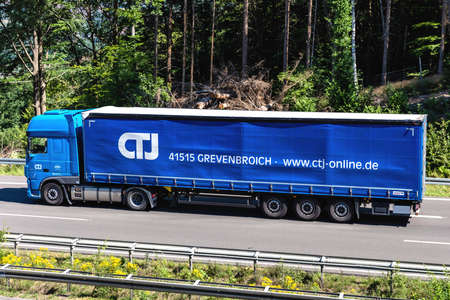 CTJ DAF XF truck with curtainside trailer on motorway. Editoriali