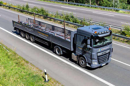 Coatinc DAF XF flatbed truck on motorway.