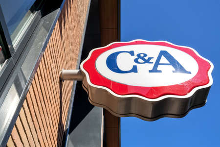 C&A sign at branch against blue sky