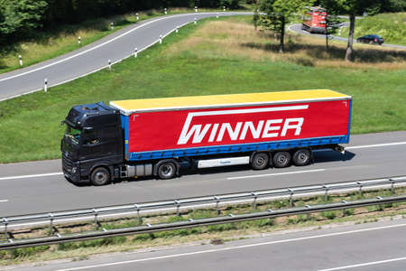 Mercedes-Benz Actros truck with Winner curtainside trailer on motorway.