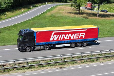 Mercedes-Benz Actros truck with Winner curtainside trailer on motorway. Archivio Fotografico - 156208165