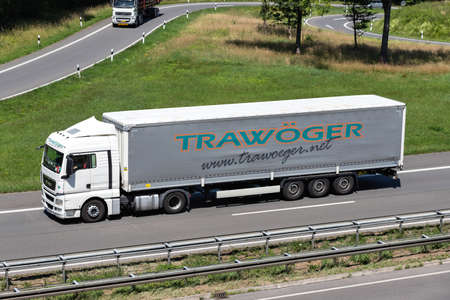 Trawöger MAN truck with curtainside trailer on motorway.