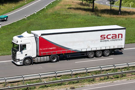 Scania truck with Scan Global Logistics curtainside trailer on motorway. Editoriali