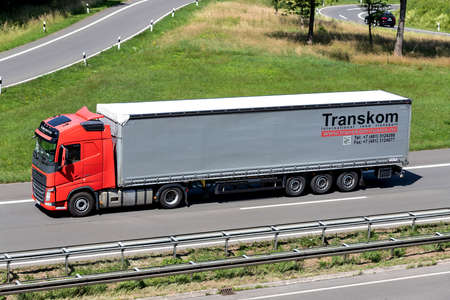 Transkom Volvo FH truck with curtainside trailer on motorway.