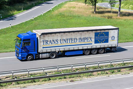 Trans United Impex MAN TGX truck with curtainside trailer on motorway.
