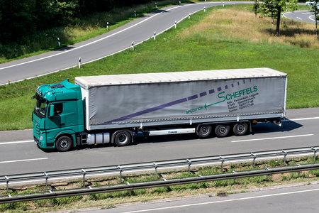 Scheffels Mercedes-Benz Actros truck with tarpaulin trailer on motorway. Archivio Fotografico - 156209967