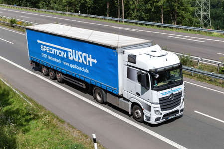 Busch Mercedes-Benz Actros truck with curtainside trailer on motorway.