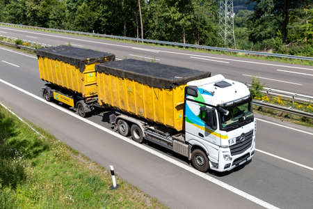 Hufnagel Mercedes-Benz Actros roll-off container truck on motorway.