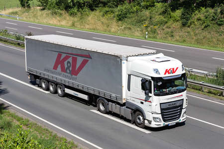 K&V DAF XF truck with curtainside trailer on motorway.