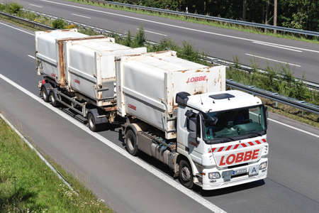 Lobbe Mercedes-Benz Actros roll-off container truck on motorway. Lobbe provides consistent service in the areas of decontamination, industrial services and disposal. Archivio Fotografico - 156764535