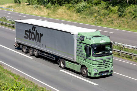Stöhr Logistik Mercedes-Benz Actros truck with curtainside trailer on motorway. Archivio Fotografico - 156764483