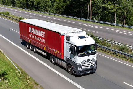 Mercedes-Benz Actros truck with Mammoet curtainside trailer on motorway. Archivio Fotografico - 156764501