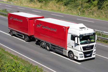 Spedition Jacobi MAN TGX combination truck on motorway. Archivio Fotografico - 156764529
