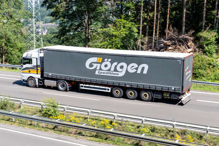 Görgen MAN TGX truck with curtainside trailer on motorway. Archivio Fotografico - 156764569