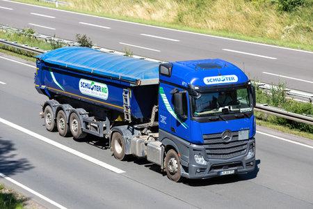 Schuster Mercedes-Benz Actros truck with tipper trailer on motorway. Archivio Fotografico - 156764517