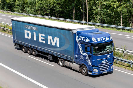 Diem DAF XF truck with curtainside trailer on motorway.