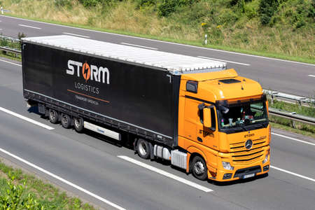 Storm Logistics Mercedes-Benz Actros truck with curtainside trailer on motorway. Editoriali