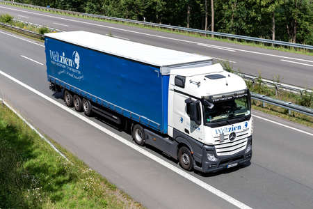 Weltzien Mercedes-Benz Actros truck with curtainside trailer on motorway.