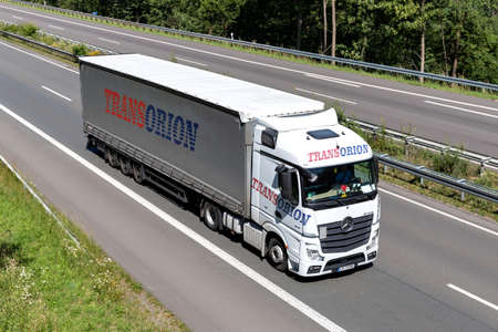 Transorion Mercedes-Benz Actros truck with curtainside trailer on motorway. Editoriali