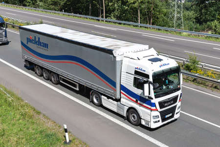 Pickhan MAN TGX truck with curtainside trailer on motorway.