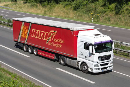 MAN Service MAN TGX truck with Kirn curtainside trailer on motorway. Editoriali