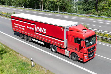 RAVE MAN TGX truck with curtainside trailer on motorway.