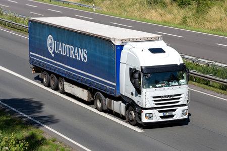Velaro Iveco Stralis truck with Quadtrans curtainside trailer on motorway. Archivio Fotografico - 156764512