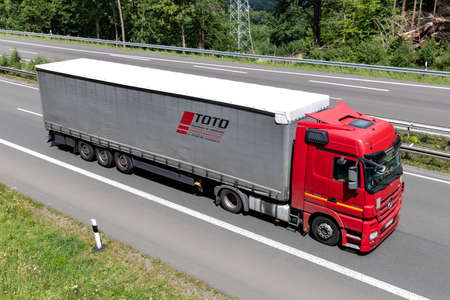 TOTO Mercedes-Benz Actros truck with curtainside trailer on motorway.