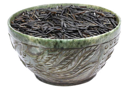 wild rice in a vintage jade bowl isolated on white background